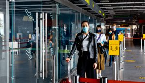 Passengers standing in line at an airport with facemasks on