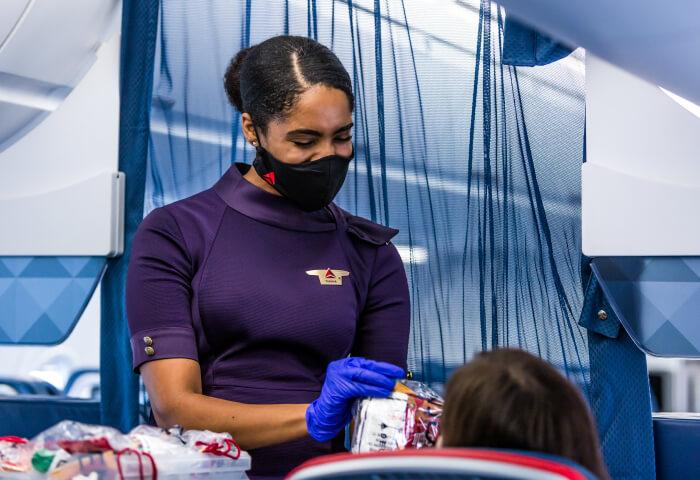 An Delta cabin crew member hands out snacks onboard a flight