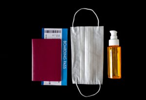 A passport, boarding pass, face mask and spray bottle