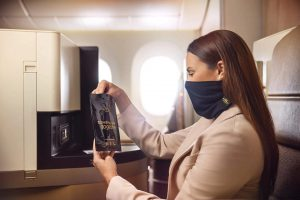 A woman wears a new Etihad Microbarrier facemask while sitting onboard a plane