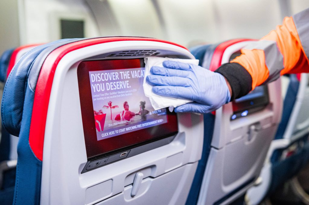 A worker wipes the seat back screen onboard an airplane seat