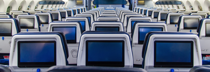 The back of plane seat with blank screens