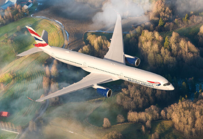 A British Airways plane flying with forest and farm land below it.