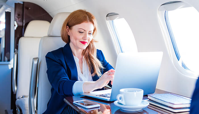 A woman types on a laptop aboard a business jet