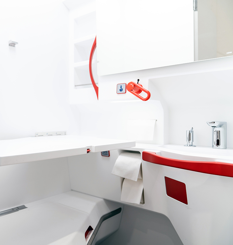 Interior of an airline lavatory with bright red handles.